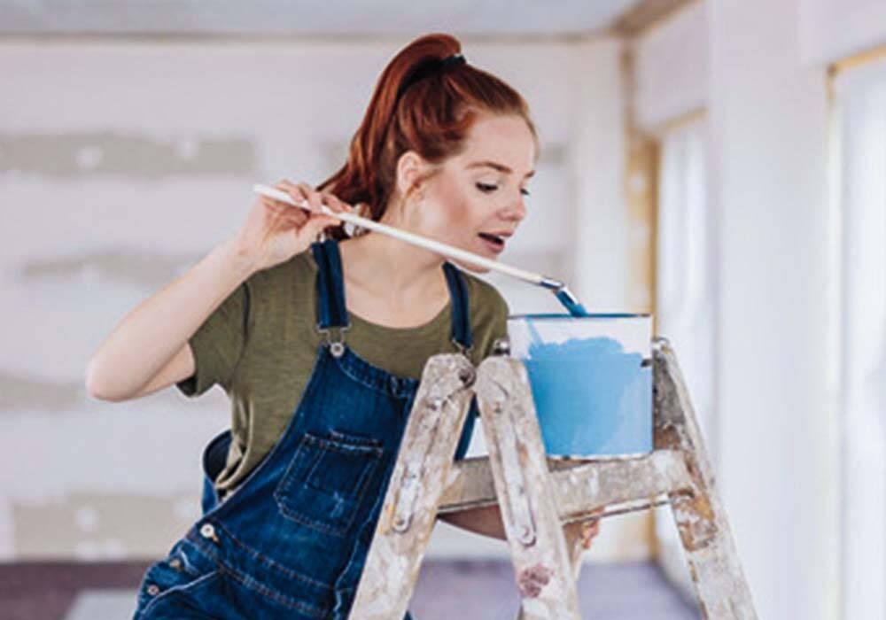 Frau beim Wohnung streichen